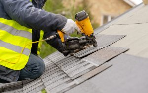 installing roofing shingles with nailgun